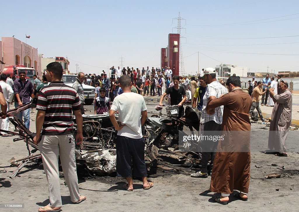 Iraqis inspect the site of a suicide car bomb attack in the Al-Haq square in Samarra, a predominantly Sunni town north of Baghdad, on July 5, 2013. Attacks killed five people in town squares in Iraq, including four who died when a suicide bomber set off his vehicle rigged with explosives just before midday prayers. / AFP / Mahmud SALEH