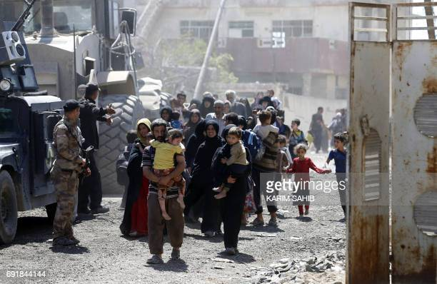 TOPSHOT Iraqis leave the Zanjili neighbourhood in west Mosul on June 3 during the ongoing offensive by security forces to retake the city from...