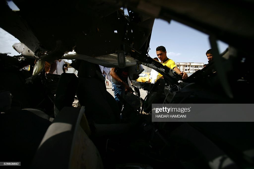 Iraqis look at a burnt out vehicle following a twin suicide bombing attack, claimed by the Islamic State (IS) group, in the southern Iraqi city of Samawah, situated deep in Iraq's Shiite heartland, on May 1, 2016. HAMDANI