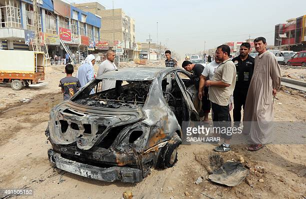 Iraqis look at a burnt vehicle on October 6 a day after a car bomb explosion in a busy area in Hosseiniyah barely 20 kilometres north of Baghdad...