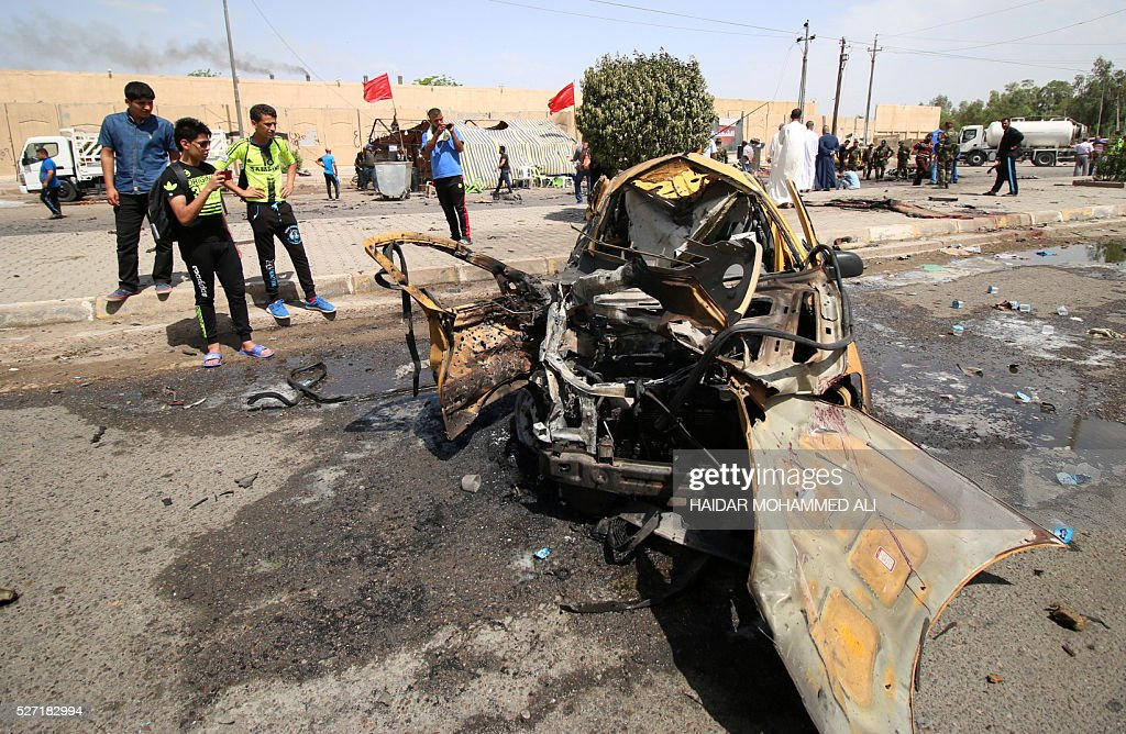 Iraqis look at the damage following a car bomb targeting pilgrims heading to commemorate the death of Imam al-Kadhim in Baghdad's southern Saidiya neighbourhood on May 2, 2106. Many of the main thoroughfares in the ca[ital are closed in the days leading up to the annual commemoration of Imam Musa Kadhim's death, an important date in the Shiite Muslim calendar. ALI