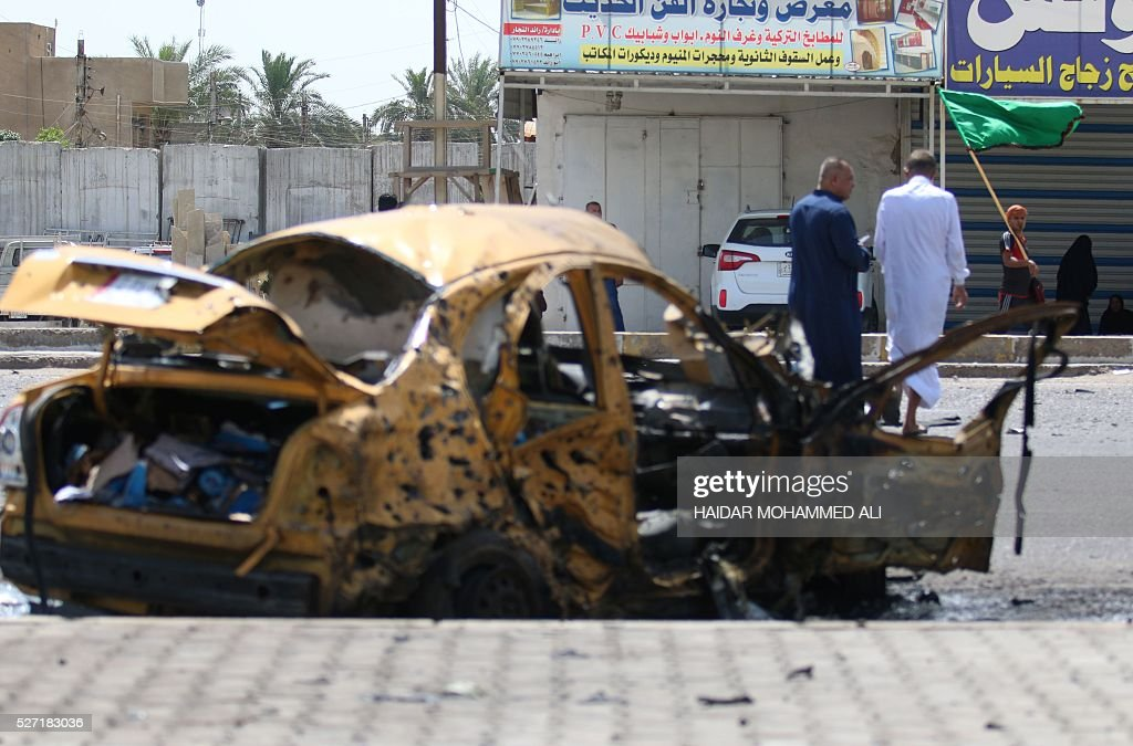 Iraqis look at the damage following a car bomb targeting Shiite pilgrims heading to commemorate the death of Imam al-Kadhim in Baghdad's southern Saidiya neighbourhood on May 2, 2106. Many of the main thoroughfares in the ca[ital are closed in the days leading up to the annual commemoration of Imam Musa Kadhim's death, an important date in the Shiite Muslim calendar. ALI