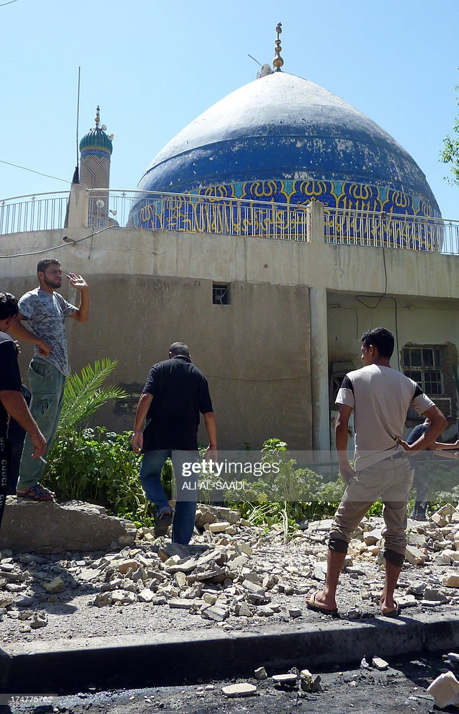 Iraqis look at the damages following a car bombing outside Ahl al-Bayya' mosque on July 29, 2013 in south eastern Baghdad. 11 car bombs hit nine different areas of Baghdad, seven of them Shiite-majority, while another exploded in Mahmudiyah to the south of the capital.