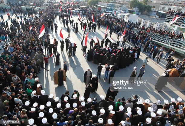 Iraqis mostly supporters of prominent cleric Moqtada Sadr take part in a mock funeral procession in Baghdad on February 14 to pay their respects to...