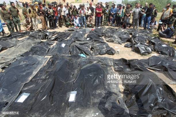Iraqis mourn near bodybags containing the remains of people believed to have been slain by jihadists of the Islamic State group lying on the ground...