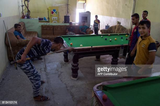 Iraqis play pool in west Mosul on July 12 2017 a few days after the government's announcement of the 'liberation' of the embattled city from Islamic...