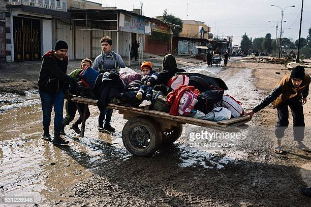 TOPSHOT Iraqis pull a cart with their belongings in a street in Mosul's alZahraa neighbourhood on January 8 as they flee with other civilians during...