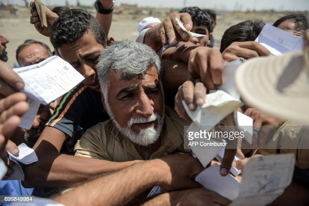 TOPSHOT Iraqis queue to receive food rations in an area outside Mosul's Old City on June 22 during the ongoing offensive by Iraqi forces to retake...