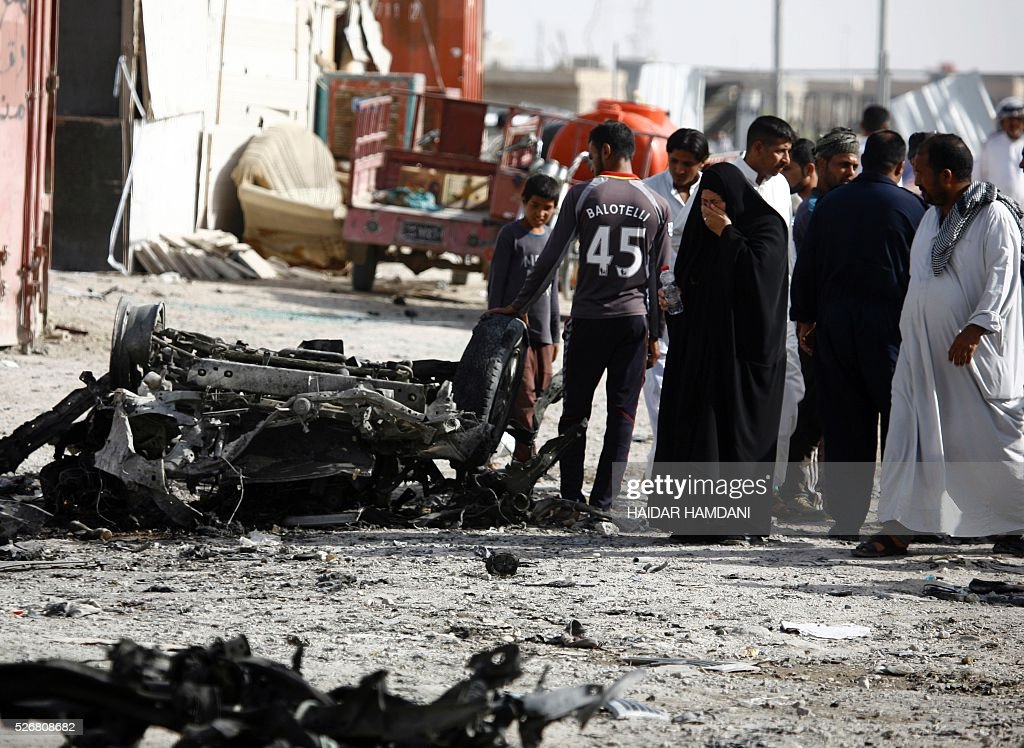 Iraqis react as they look at the damage following a twin suicide bombing attack, claimed by the Islamic State (IS) group, in the southern Iraqi city of Samawah, situated deep in Iraq's Shiite heartland, on May 1, 2016. HAMDANI