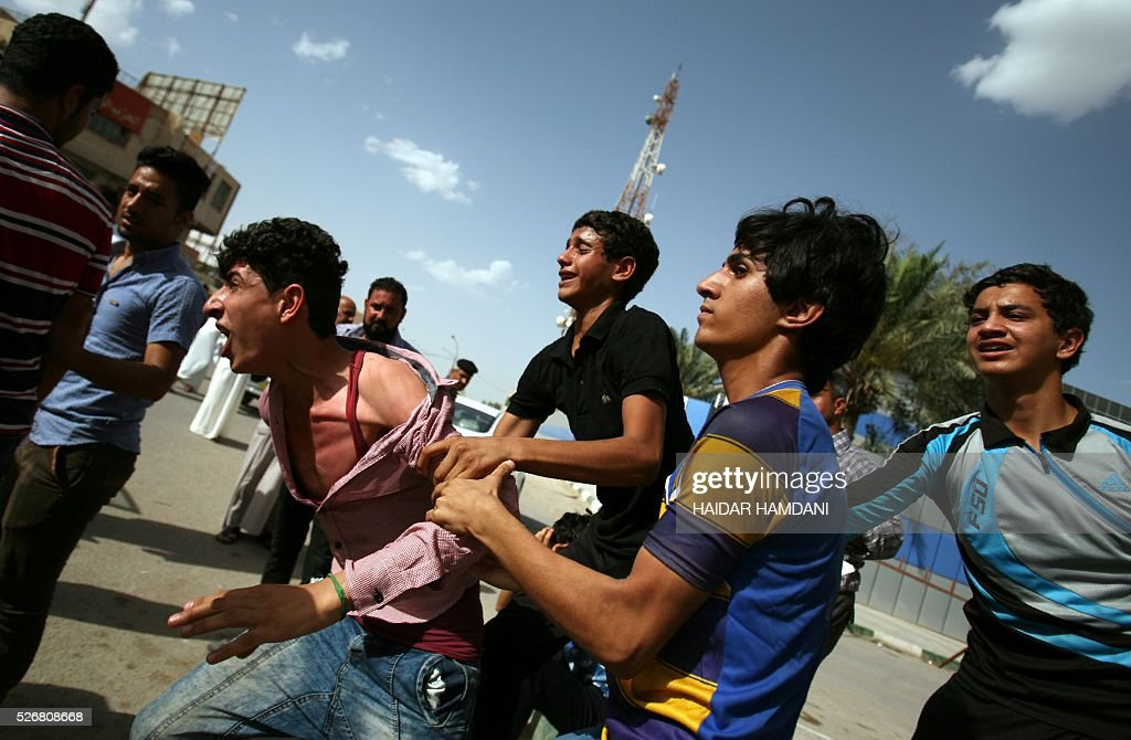 Iraqis react at the site of a twin suicide bombing attack, claimed by the Islamic State (IS) group, in the southern Iraqi city of Samawah, situated deep in Iraq's Shiite heartland, on May 1, 2016. HAMDANI