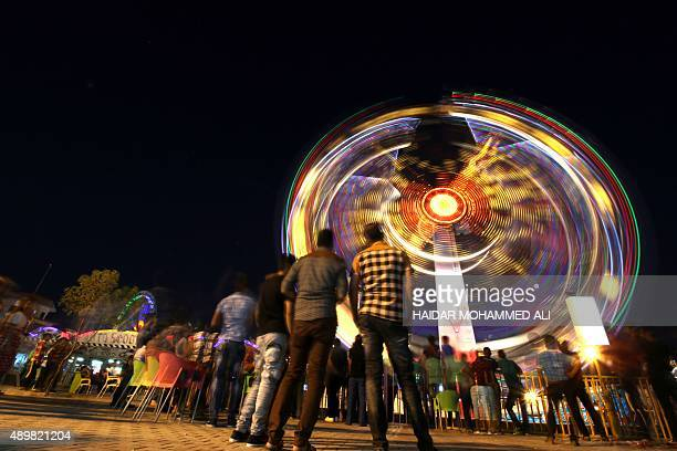 Iraqis ride a ferris wheel at an amusement park in the southern city of Basra on the first day of the Muslim Eid alAdha holiday on September 24 2015...