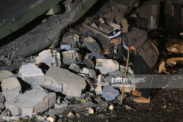 Iraqis search for the trapped citizens over the collapsed buildings after a 73 magnitude earthquake hit northern Iraq in Derbendihan district of...