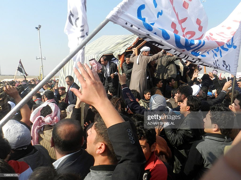 Iraqis serge towards the stage where Iraqi deputy premier Saleh al-Mutlak arrived to give a speech on December 30, 2012, forcing him to flee a rally he was addressing on the outskirts of the western city of Ramadi, an AFP reporter said. The demonstrators, who have blocked a key highway connecting Iraq to Syria and Jordan for the past week over the alleged targeting of their Sunni Arab minority by the Shiite-led government in Baghdad, threw water bottles, stones and shoes at Mutlak before grabbing and hitting him. AFP PHOTO/AZHAR SHALLAL