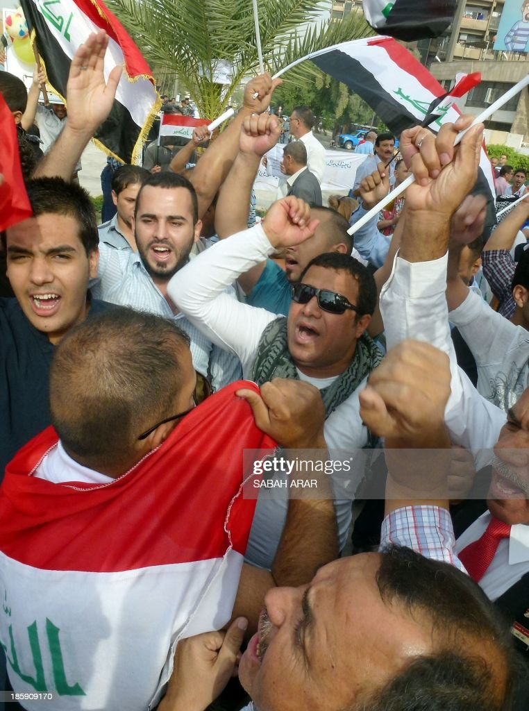 Iraqis shout slogans and wave national flags as they take part in a demonstration against privileges of MPs and seniors officials, on Firdous Square in the centre of Baghdad, on October 26, 2013.