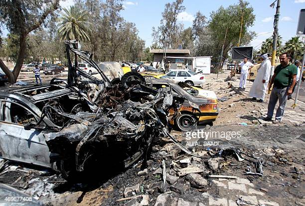 Iraqis stand at the site of an explosion at the car park across the street from the alYarmuk hospital in the west of Baghdad on April 14 2015...