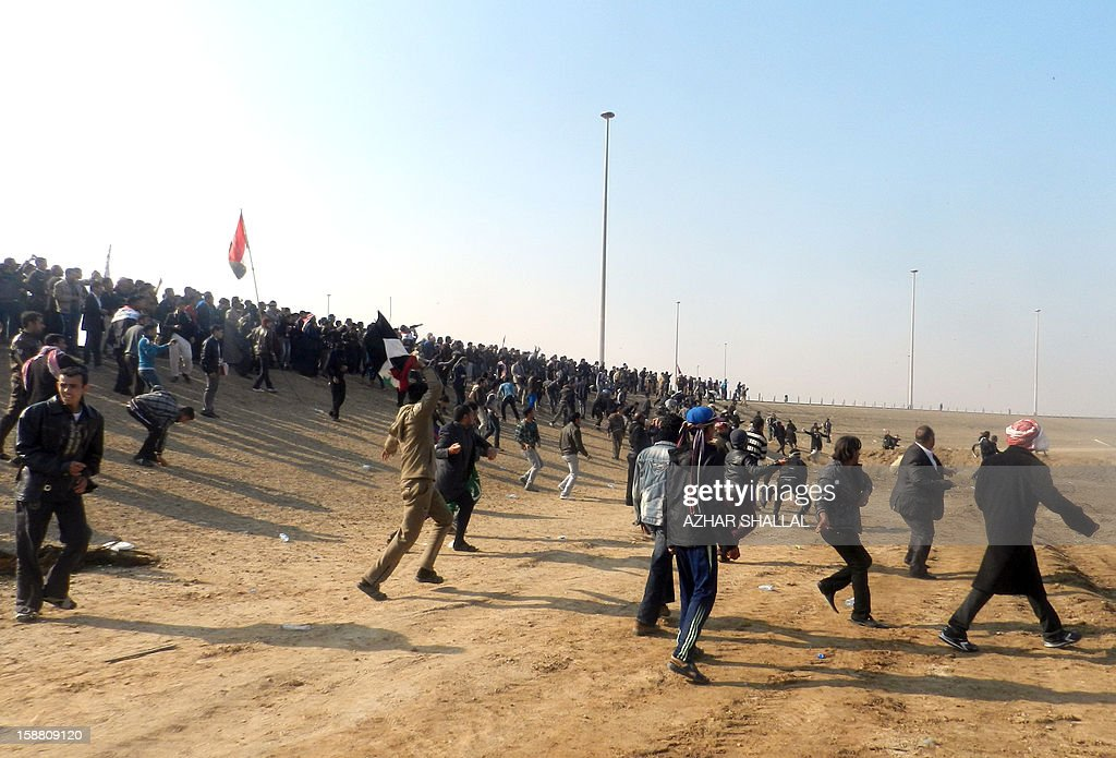 Iraqis throw stones after protesters attacked Iraq's deputy premier Saleh al-Mutlak on December 30, 2012, forcing him to flee a rally he was addressing on the outskirts of the western city of Ramadi, an AFP reporter said. The demonstrators, who have blocked a key highway connecting Iraq to Syria and Jordan for the past week over the alleged targeting of their Sunni Arab minority by the Shiite-led government in Baghdad, threw water bottles, stones and shoes at Mutlak before grabbing and hitting him. AFP PHOTO/AZHAR SHALLAL