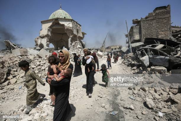 Iraqis walk by the destroyed AlNuri Mosque as they flee from the Old City of Mosul on July 5 during the Iraqi government forces' offensive to retake...