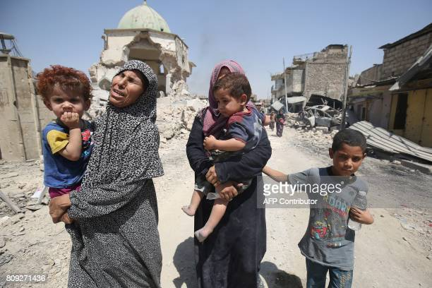 TOPSHOT Iraqis walk by the destroyed AlNuri Mosque as they flee from the Old City of Mosul on July 5 during the Iraqi government forces' offensive to...