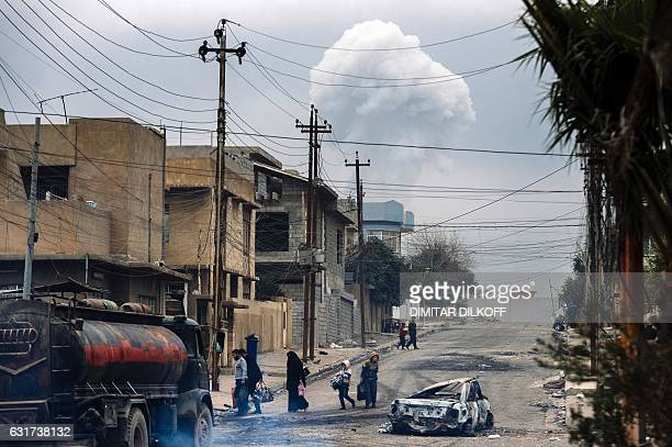 Iraqis walk down a street while smoke rises in the background following a car bomb explosion in eastern Mosul on January 15 during an ongoing...