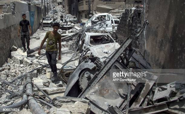 TOPSHOT Iraqis walk in the Old City of Mosul on July 3 2017 during an ongoing offensive to retake the city from Islamic State group fighters Iraqi...