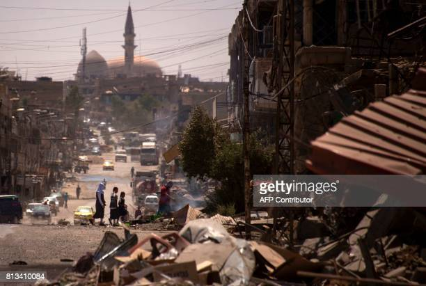 TOPSHOT Iraqis walk on a damaged street in west Mosul on July 12 2017 a few days after the government's announcement of the 'liberation' of the...