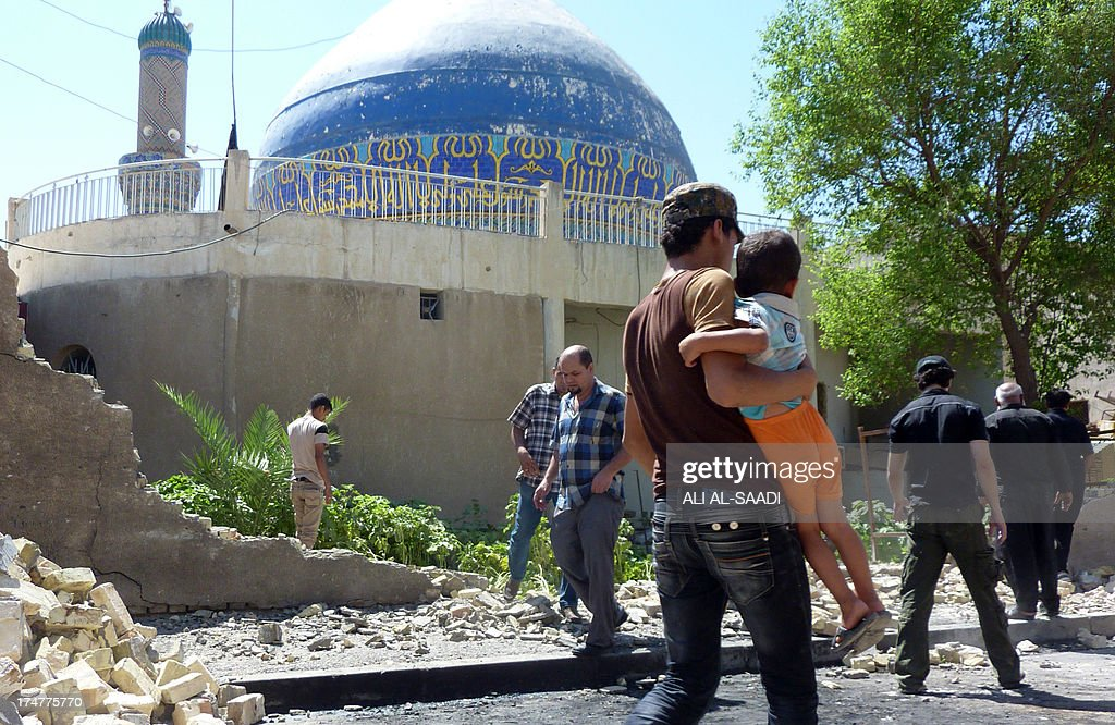 Iraqis walk past a wall that was destroyed in a car bombing outside Ahl al-Bayya' mosque on July 29, 2013 in south eastern Baghdad. 11 car bombs hit nine different areas of Baghdad, seven of them Shiite-majority, while another exploded in Mahmudiyah to the south of the capital.