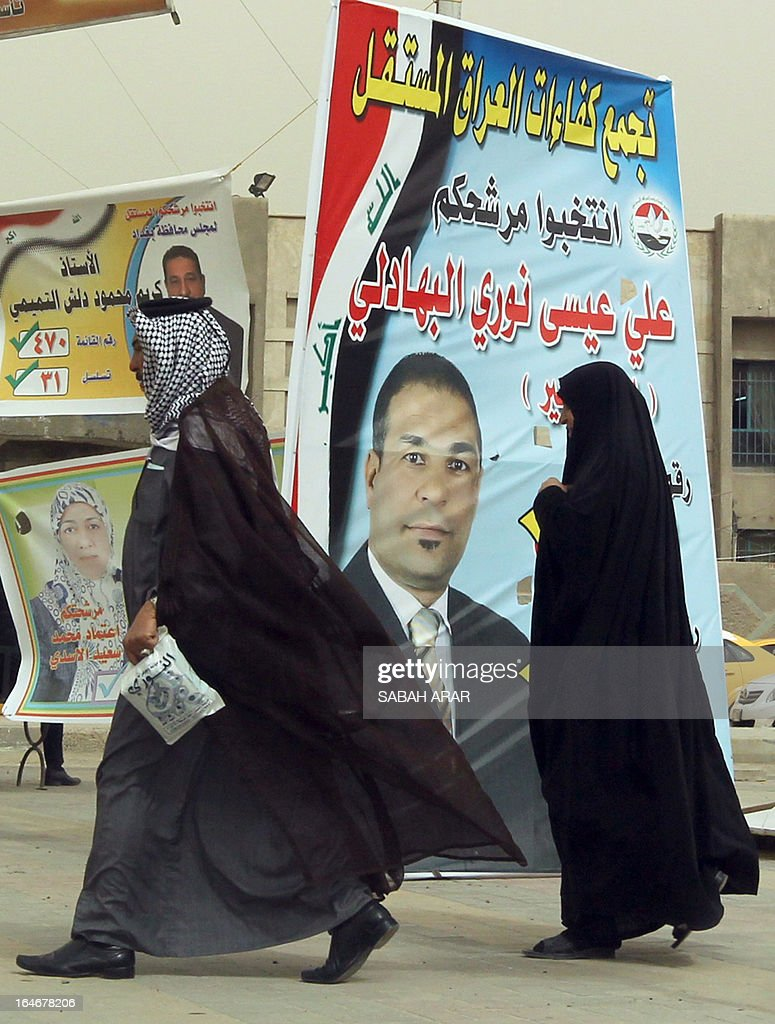 Iraqis walk past the electoral campaign banner of a candidate running in the upcoming provincial elections in Baghdad on March 25, 2013. Baghdad and much of Iraq has been plastered with posters, ranging from the ordinary to the bizarre, of election candidates vying for voters' attention ahead of provincial elections next month. Judging by the slogans and appeals on many of the posters, analysts and commentators note, Iraqi political campaigning still has a long way to go, with most making no mention of ideology or policies and many not even featuring the candidate running for office. AFP PHOTO/ SABAH ARAR