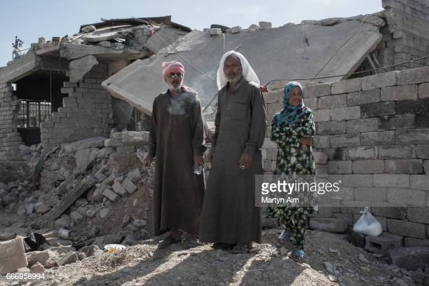 Iraqis watch Iraqi forces pass their destroyed house in Al Yarmuk west Mosul April 10 2017 Iraqi forces retook the district While Coalition air...