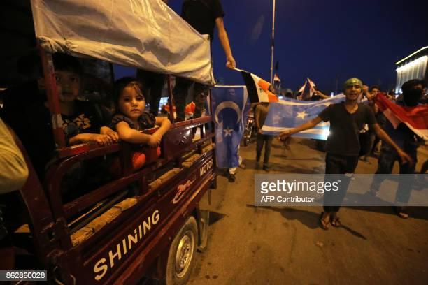 Iraqis wave their national flag and flags of the flag of the Iraqi Turkmen people as they gather in the street in the city of Kirkuk to celebrate on...