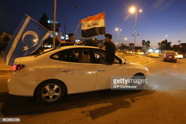 Iraqis wave their national flag and the flag of the Iraqi Turkmen people as they drive in the street in the city of Kirkuk to celebrate on October 18...