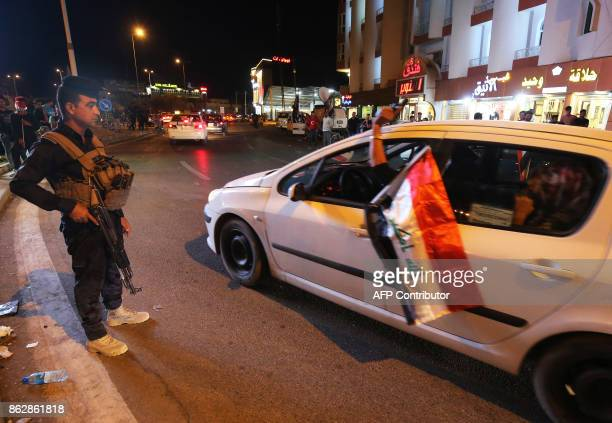 Iraqis wave their national flag as they celebrate in the city of Kirkuk on October 18 after Iraqi government forces retook almost all the territory...