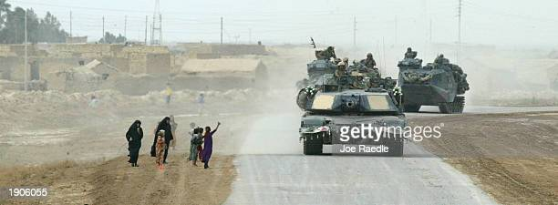 Iraqis wave to a US Marine M1A1 tank of Task Force Tarawa as it passes April 8 2003 through their village as the Marines move through central Iraq...