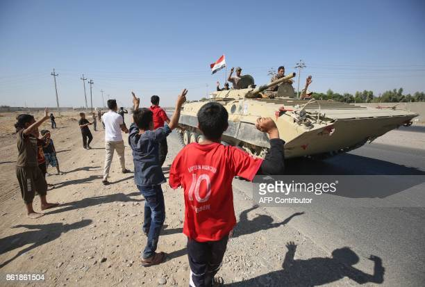TOPSHOT Iraqis wave to Iraqi forces as they arrive in the first neighbourhood on the southern outskirts of Kirkuk on October 16 2017 Iraqi forces...