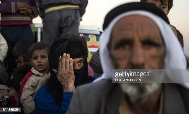 TOPSHOT CORRECTION Iraqis who fled their village due to the fighting in Mosul are escorted to safety by forces from Iraq's elite Rapid Response...