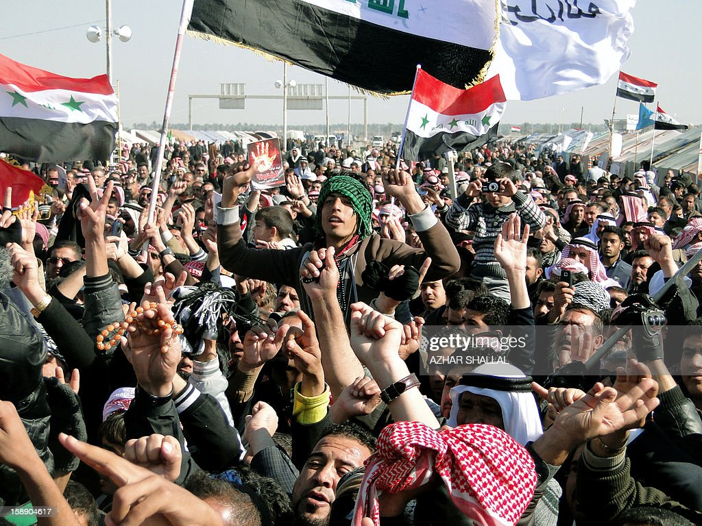 Iraqi-Sunni protestors and Shiite demonstrators from the Karbala provinces and the Baghdad Shiite suburb of Sadr City wave their hands in the air during a demonstration in the western city of Ramadi calling for the release of prisoners and the resignation of the Iraqi Shiite premier on January 3, 2013. Officials sought to head off the demonstrations against Iraqi Prime Minister, Nuri al Malaki, by beginning a mass release of female prisoners, a key demand of Sunni Arab protesters angered by what they allege is the misuse of anti-terror legislation by the Shiite-led authorities to target their minority community. AFP PHOTO / AZHAR SHALLAL