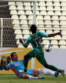Iraq's alShorta club player Amjed Kalaf scores a goal as Syria's AlWahda goalkeeper Mahmoud Karkar tries to save the ball during their AFC Cup Group...