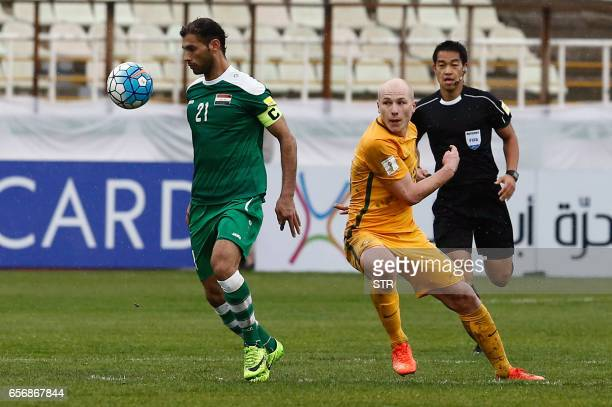 Iraq's captain and midfielder Saad AbdulAmir controls the ball as he is marked by Australia's midfielder Aaron Mooy during the FIFA World Cup 2018...