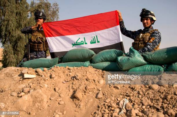 Iraq's federal police members hold Iraq's national flag as they celebrate in the Old City of Mosul on July 9 2017 after the government's announcement...