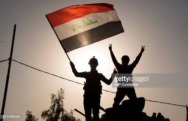 TOPSHOT Iraq's federal police members wave Iraq's national flag as they celebrate in the Old City of Mosul on July 9 2017 after the government's...