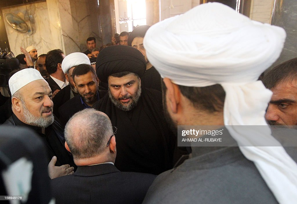 Iraq's maverick Shiite cleric Muqtada al-Sadr (C) speaks to Sunni clerics during Friday prayers in which Sunni and Shiite Muslim worshippers took part together in a gesture of unity at the Abdul Qadir Gilani Mosque in Baghdad on January 4, 2013, as protests in Sunni-majority areas across the country were planned to call for the release of prisoners and criticise Nuri al-Maliki's Shiite-led government.