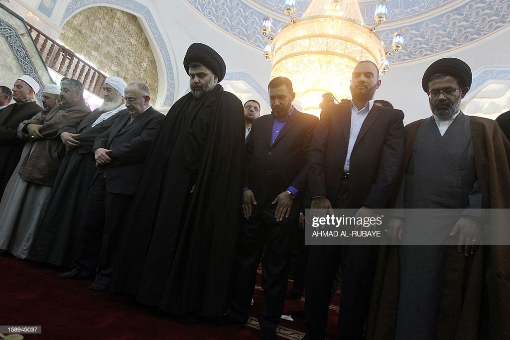 Iraq's maverick Shiite cleric Muqtada al-Sadr (C) takes part in Friday prayers in which Sunni and Shiite Muslim worshippers took part together in a gesture of unity at the Abdul Qadir Gilani Mosque in Baghdad on January 4, 2013, as protests in Sunni-majority areas across the country were planned to call for the release of prisoners and criticise Nuri al-Maliki's Shiite-led government.