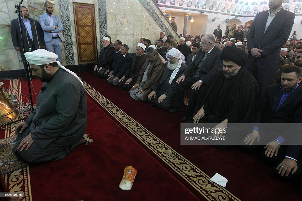 Iraq's maverick Shiite cleric Muqtada al-Sadr (back-C) takes part in Friday prayers in which Sunni and Shiite Muslim worshippers took part together in a gesture of unity at the Abdul Qadir Gilani Mosque in Baghdad on January 4, 2013, as protests in Sunni-majority areas across the country were planned to call for the release of prisoners and criticise Nuri al-Maliki's Shiite-led government. AFP PHOTO / AHMAD AL-RUBAYE
