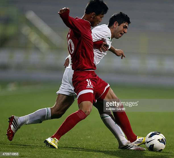 Iraq's Mohannad AbdulRaheem is defended by North Korea's Ri Hyon Jin during their friendly football match at AlWassal stadium on February 21 2014 in...