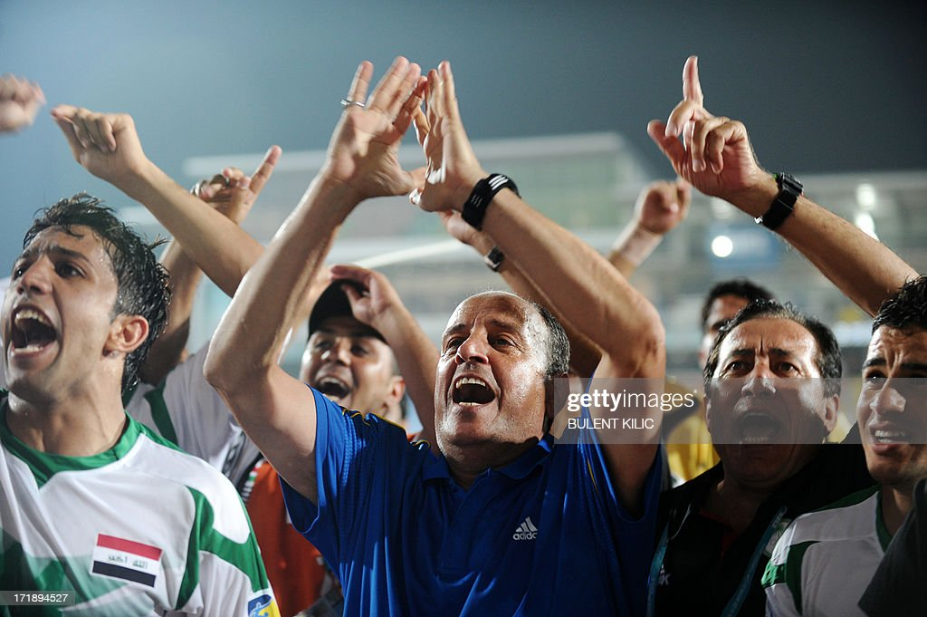 Iraq's players and their head coach Hakeem Al Azzawi (C) celebrate their victory at the end of a group stage football match Iraq vs Chile at the FIFA Under 20 World Cup at Akdeniz University Stadium in Antalya on June 29, 2013.