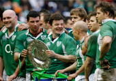Ireland captain Brian O'Driscoll celebrates with teammates and the Triple Crown trophy following his team's victory during the RBS Six Nations...