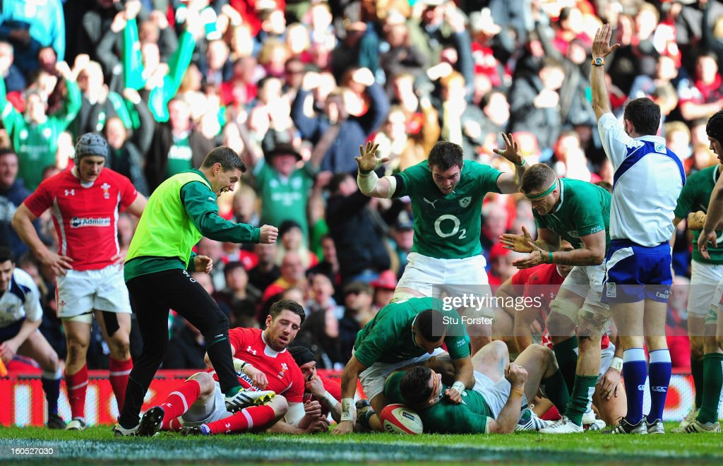 Ireland celebrate their second try scored by <a gi-track='captionPersonalityLinkClicked' href=/galleries/search?phrase=Cian+Healy&family=editorial&specificpeople=4166531 ng-click='$event.stopPropagation()'>Cian Healy</a> (floor) as the Wales players Alex Cuthbert (l) and Mike Phillips look on dejectedly during the RBS Six Nations game between Wales and Ireland at the Millennium Stadium in Cardiff, Wales.