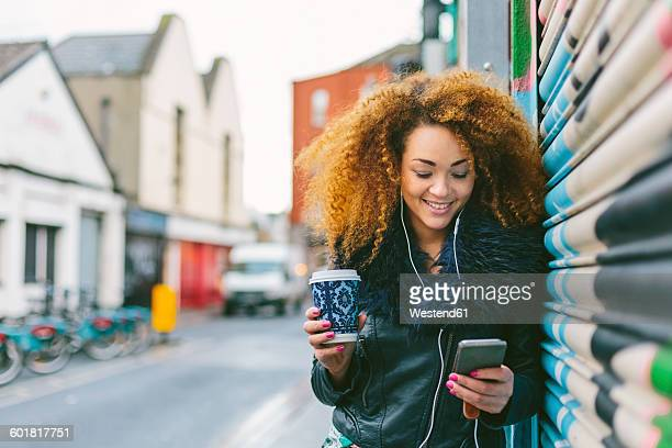 Ireland, Dublin, smiling woman with coffee to go hearing music with smartphone and earphones