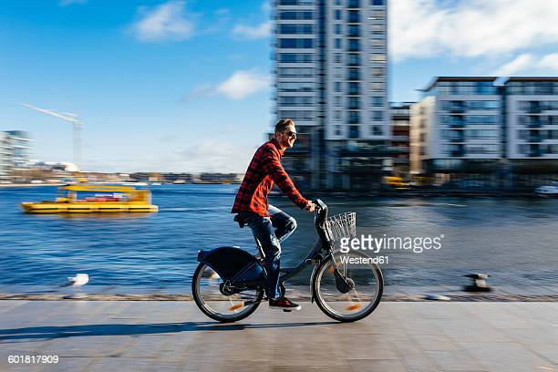 Ireland, Dublin, young man at city dock riding city bike