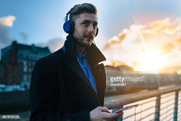 Ireland, Dublin, young man hearing music with headphones at twilight