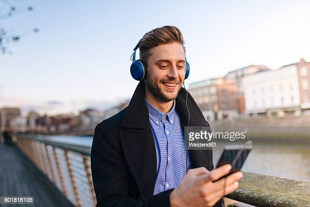 Ireland, Dublin, young man holding smartphone hearing music with headphones